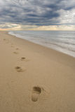 Footprints on a sandy beach, dark stormy clouds. Lonely footprints on a sandy beach, under dark stormy clouds at sunset stock photos