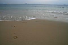 Footprints on a sandy beach, Ship on the horizon Stock Images