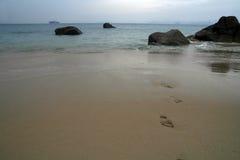 Footprints on a sandy beach, Ship on the horizon Stock Photos