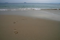 Footprints on a sandy beach, Ship on the horizon Royalty Free Stock Images