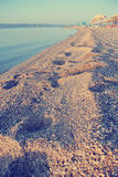 Footprints on the sandy beach in summer; faded, retro style Royalty Free Stock Images