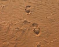 Footprints on sandy desert. Human footprints on red sandy desert with rippled effect stock photos