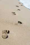 Footprints on sea beach sand with wave foam Stock Images