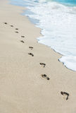 Footprints on sea beach sand with wave foam Stock Photos