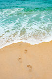 Footprints in the sea sandy beach , wave foam  on a vacation tim Stock Photo