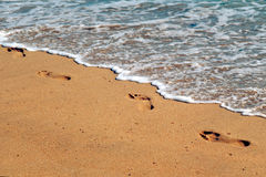 Footprints at the seashore. Footprints at the sunny seashore Stock Photo