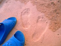 Footprints and shoes on the sand Royalty Free Stock Images