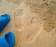 Footprints and shoes on the sand Stock Photography