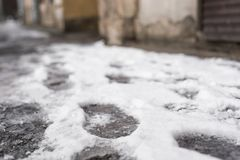 Footprints from shoes in the snow on the street close, soft focus. Footprints from shoes in the snow on the street close Royalty Free Stock Photos