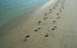 Footprints on the shore. Couple leaves a lasting impression of their walk along the beach stock photography