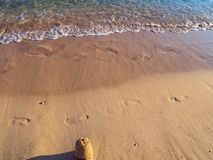 Footprints and small sand castle on the empty beach - calm small waves royalty free stock images