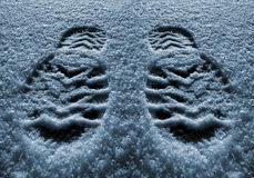 Footprints in the snow. Men's track shoes with snow cover Stock Image