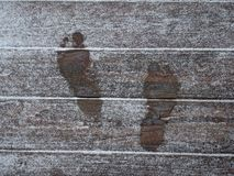 Footprints in The Snow. On a wooden deck causing the snow to melt Royalty Free Stock Image