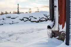Footprints in snow. Downpipes with icicles and snow covered stone wall, footprints in snow Stock Image