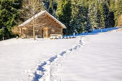 Footprints in snow leading to old wooden cabin and forest. Allgau, Bavaria, Germany, Alps. Stock Images