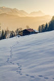 Footprints in snow towards wooden cabin in mountains of Allgau Royalty Free Stock Photography