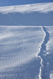 Footprints in a snowy landscape. Mountain panorama of the snow in a sunny winter day Stock Images