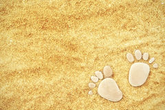 Footprints of stones on yellow sand on the beach in summer Stock Photo