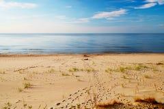 Footprints on a sunny, empty beach. Stock Image