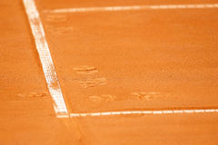 Footprints on a tennis clay court Stock Photos