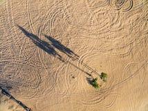 Footprints, tracks and shadows on sand Royalty Free Stock Photo