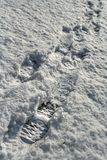 Footprints of trekking boots in snow sunlit by afternoon winter sun. Footprints of trekking boots in snow. Photo is sunlit by afternoon winter sun stock photos