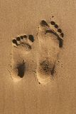 Footprints of two. Two different size footprints on beach Stock Image