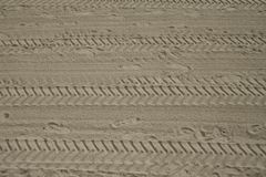 Footprints and tyre tracks in sand Stock Images