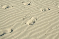 Footprints in the wavy sand. A path of raised shoe footprints in wavy sand on a beach Royalty Free Stock Images