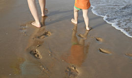 Footprints in wet sand. Leaving footprints in the wet sand - seen from behind mother and son (legs visible Stock Photography