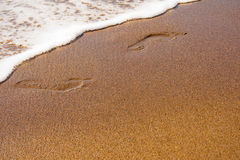 Footprints in wet sand. Footprints in wet and grainy beach sand with sea water near Stock Photo