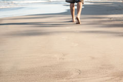 Footprints in wet sand of beach. Walk Stock Image
