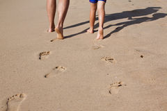 Footprints in wet sand of father and son. Walking on the beach together Stock Photo