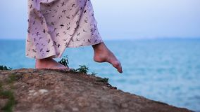 Foots of girl in Light Dress Walking at the Enge of Cliff above the Sea at Sunrise time. Slow Motion stock video footage