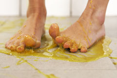 Foots in slime. Young woman playing with melted Jelly in white tile room Stock Photo