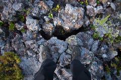 Foots stående near stora sprickor i karga lavafält royaltyfria foton