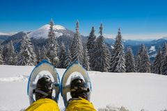 Foots traveler in snowshoes. Against the background of snow-capped mountains on a sunny day. Epic adventure in winter wilderness Stock Photos