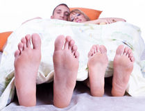 Foots of young couple lying in bed Royalty Free Stock Photos