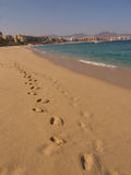 Footsteps on the beach. With hotels and mountains in the background. Calm blue sea and wet sand Stock Photo