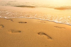 Footsteps on the beach by the sea Stock Images