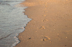 Footsteps on the beach by the sea Stock Photo