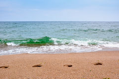 Footsteps on the beach by the sea in summer Stock Photos