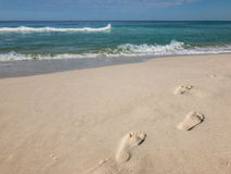 Footsteps on the beach. Footsteps on the shore with waves Royalty Free Stock Images