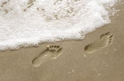 Footsteps in the sand. Footsteps on the beach as surf moves in Stock Images