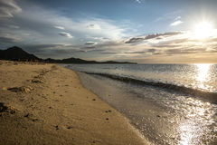 Footsteps in sand on a beach. Empty beach early in the morning  in Costa Rei, Sardinia, Italy. Beautiful clouds, sunrise and fresh footsteps in the sand. Nobody Stock Photos