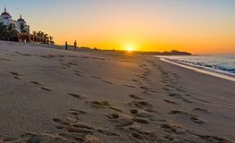 Footsteps in sand on beach at sunrise. Sunrise on sandy beach with footsteps leading to distance Royalty Free Stock Images