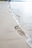 Footsteps on sand beach, wave Royalty Free Stock Image