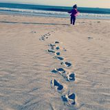 Footsteps in the sand. Child toddler walking in the sand on the beach Stock Photography