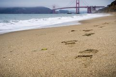 Footsteps on the sand, Golden Gate bridge in the background, California. Footsteps on the sand, Golden Gate bridge in the background; foggy day, California Royalty Free Stock Photography