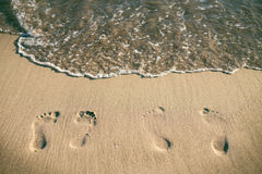 Footsteps on a sandy beach. Wave and sun. Holiday and travel concept. Summer vibes. Footsteps on a sandy beach. Wave and sun. Holiday and travel concept. Summer Stock Photo